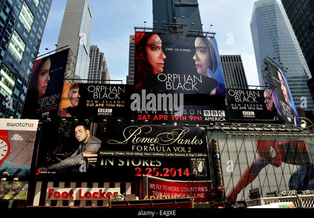 New York City: Giant advertising billboards cover building facades overlooking legendary Times Square - Stock Image
