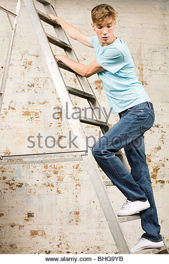 Teenage boy on a ladder - Stock Image