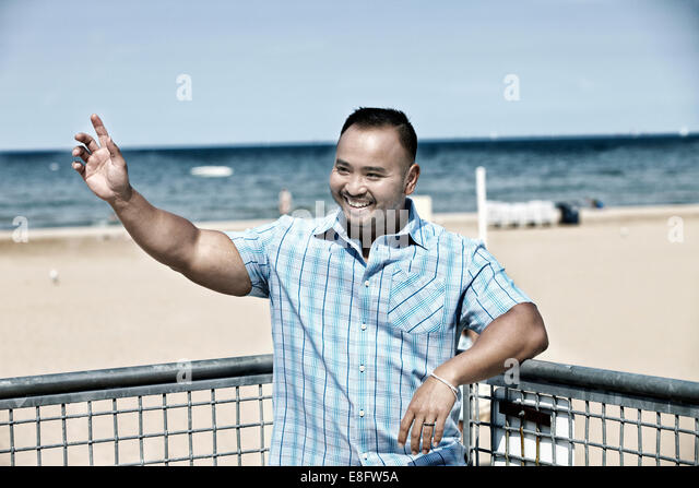USA, Illinois, Cook County, Chicago, Man waving on beach - Stock Image