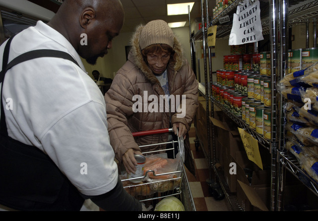 A client shops for groceries with a worker at the Food Bank of NYC Food Pantry in the Harlem neighborhood of New - Stock Image