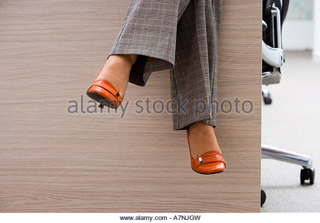 Businesswoman wearing checked grey trousers and orange high heels sitting on desk in office low section - Stock Image