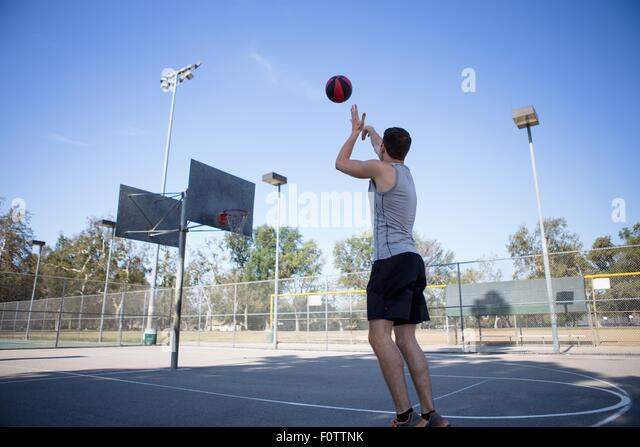 Young male basketball player throwing ball toward basketball hoop - Stock Image
