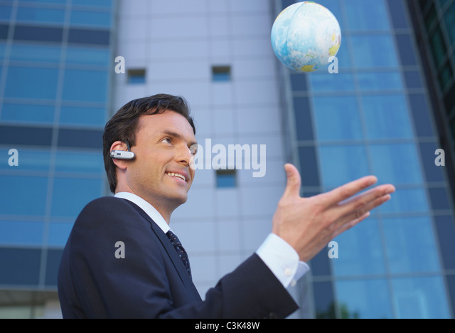 Germany, Munich, Manager with small globe - Stock Image