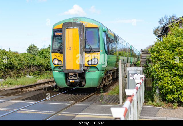 Green and Yellow Southern train approaching a level crossing in England, UK. Southern trains. Southern Rail. - Stock Image