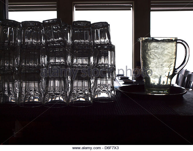 Drinking water glasses and jug - Stock Image