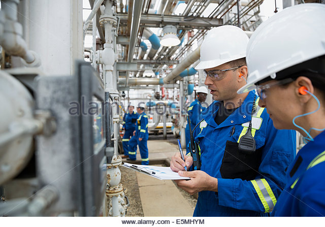 Workers checking equipment at gas plant - Stock Image