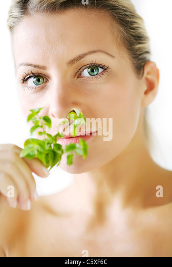 female smelling mint branch, focus is on the eyes, not on the plant - Stock Image