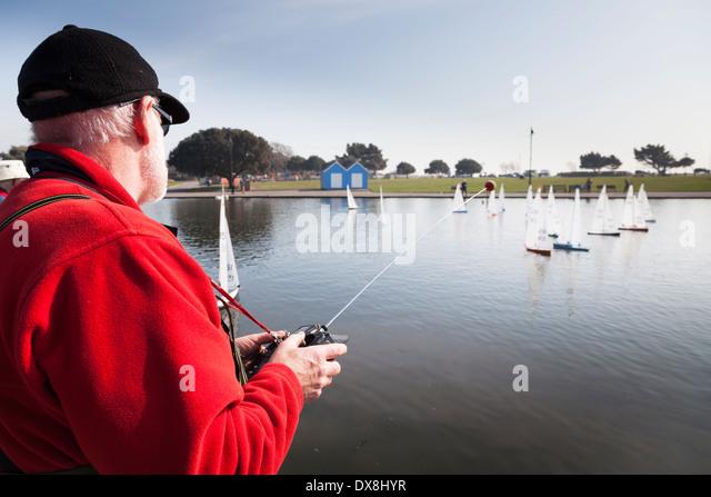 Radio controlled model yacht enthusiasts racing on Canoe Lake Southsea. - Stock Image