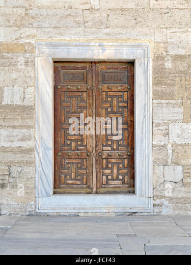 Wooden aged vaulted engraved door and exterior stone wall, Sultan Ahmet Mosque, Istanbul, Turkey - Stock Image