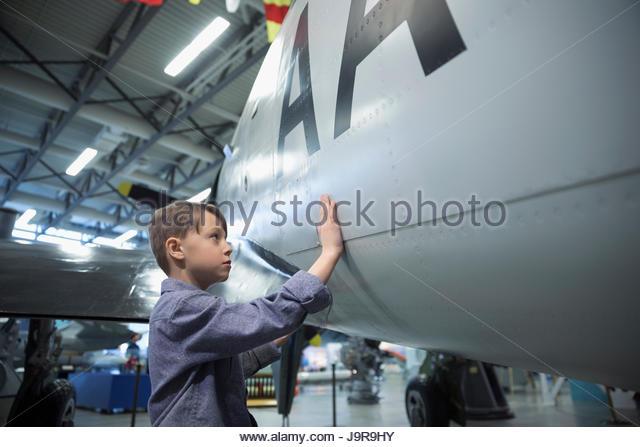 Curious boy touching Air Force airplane in war museum hangar - Stock-Bilder