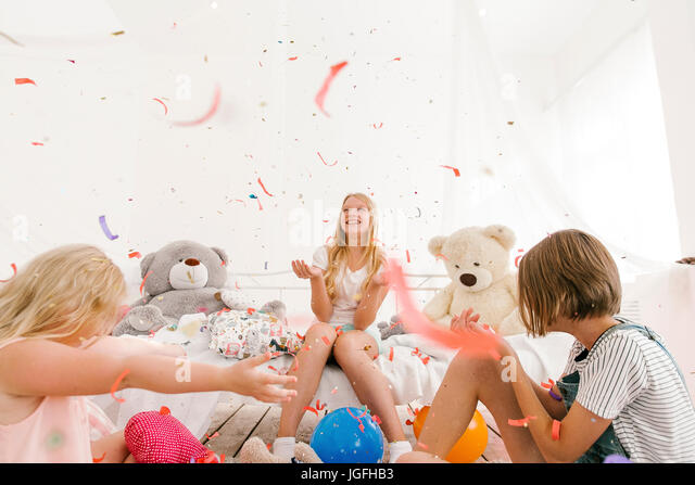 Middle Eastern sisters throwing confetti in bedroom - Stock Image