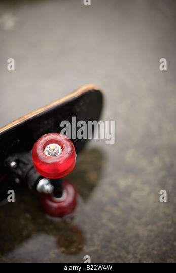 Skateboard in puddle - Stock-Bilder