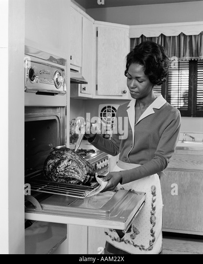 1970s BLACK WOMAN AFRICAN AMERICAN OVEN TURKEY THANKSGIVING - Stock Image