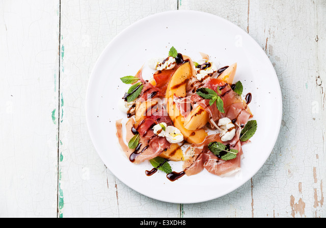 Melon and prosciutto ham salad with Mozzarella and mint leaves - Stock Image