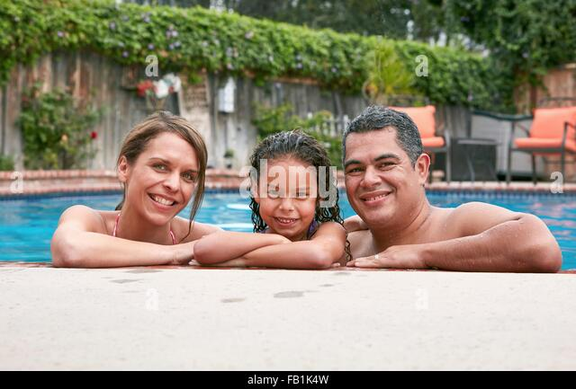 Head and shoulders of girl in swimming pool with parents looking at camera smiling - Stock Image