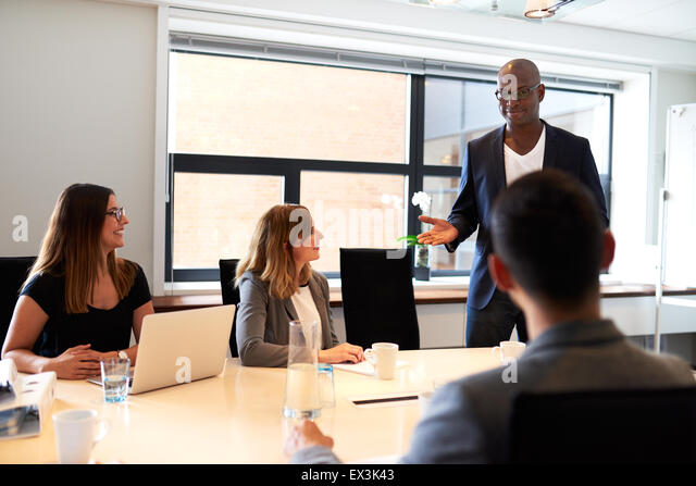 Black male executive standing and leading a work meeting in conference room. - Stock Image