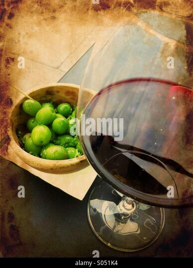 Nostalgia with glass of red wine and fresh green olives - Stock Image