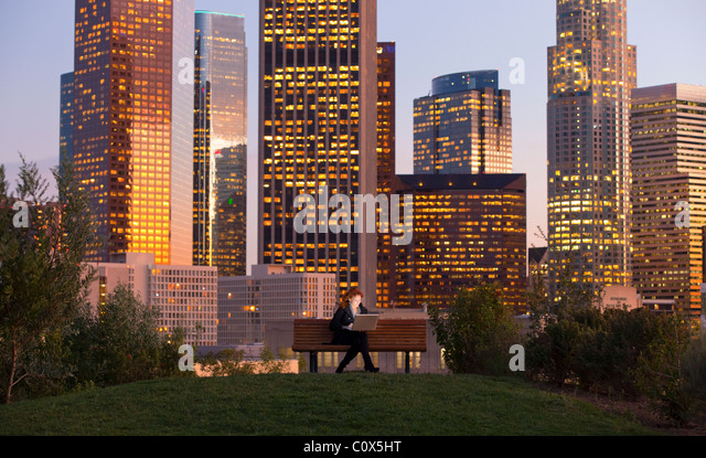 Female sitting on park bench working on laptop computer with Los Angeles city skyline in background at dusk, sunset - Stock-Bilder