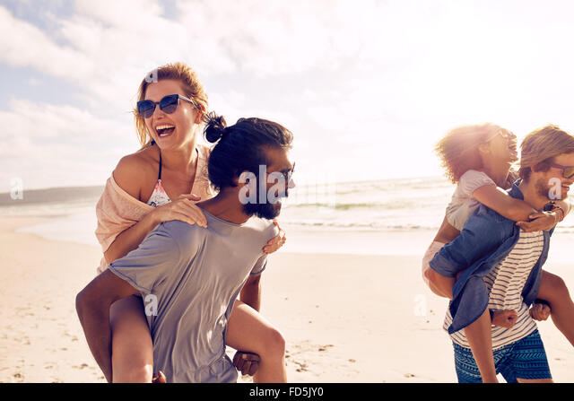 Happy young men giving piggyback ride to women on beach. Diverse group of young people having fun on the beach and - Stock Image