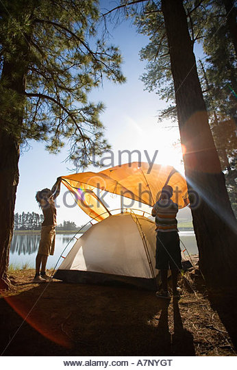 Father and son 8 10 assembling orange tent on lakeside camping trip lens flare - Stock Image