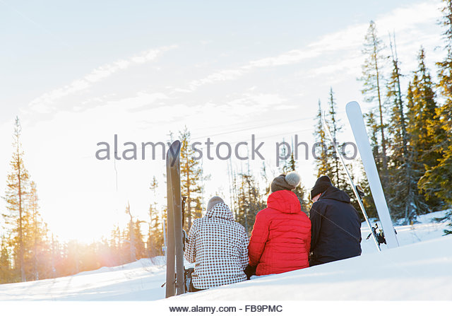 Sweden, Harjedalen, Vemdalen, Klovsjo, Father and two daughters sitting together on ski slope - Stock Image