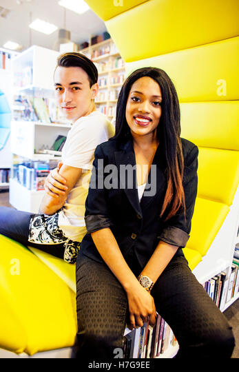 couple students in univercity library, looking book, preparing to exam, having fun, making selfie, lifestyle people - Stock Image
