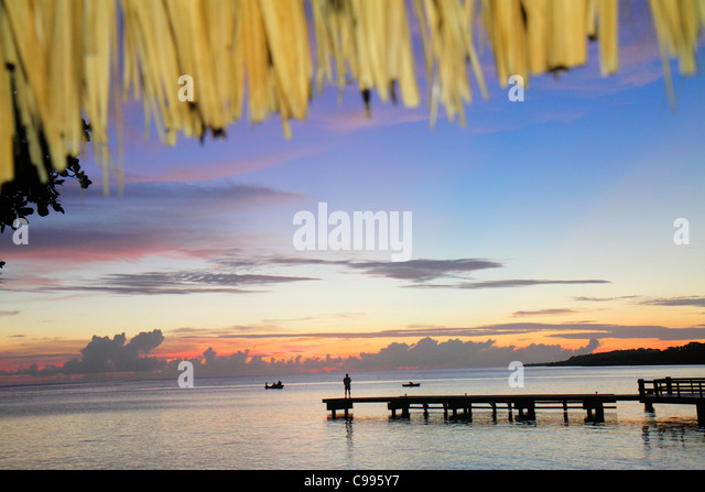 Curaçao Netherlands Antilles Dutch Piscadera Bay Caribbean Sea pier man standing boat coastline sunset twilight - Stock Image