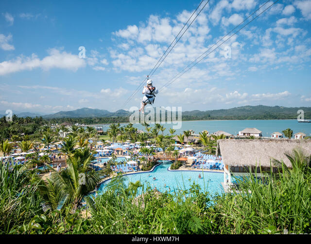 Woman on Zipwire above Amber Cove Cruise Resort Dominican Republic Caribbean with Cruise ship Azura in background. - Stock Image
