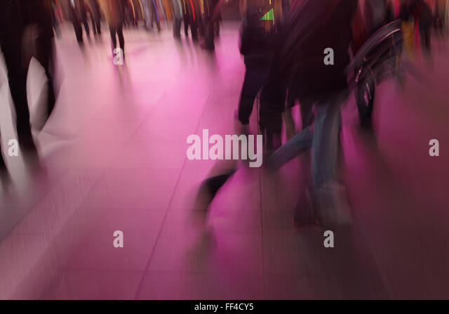 Abstract blurred people walking in Times Square New York City long exposure photograph with neon lights background - Stock Image