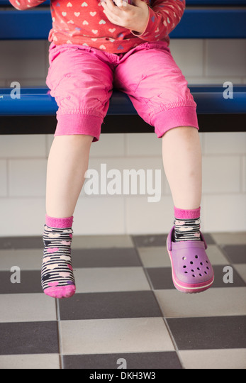 Young girl wearing one shoe sitting alone on a bench - Stock Image