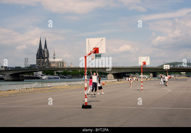 School children playing basketball beside the river Rhine, Cologne, Germany. - Stock Image