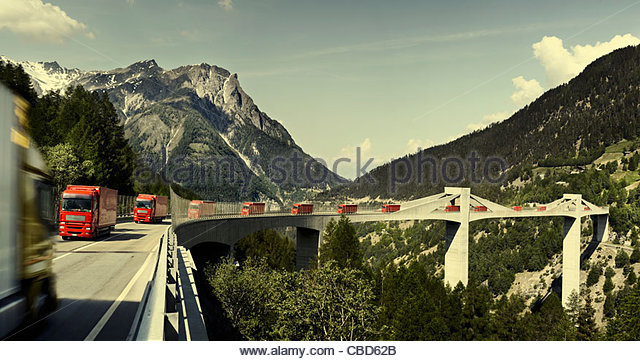 Trucks driving on bridge in mountains - Stock Image
