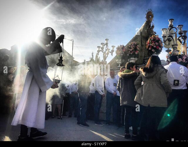 An altar boy spreads incense during a  procession of Our Lady of Carmel in Prado del Rey, Sierra de Cadiz, Andalusia, Spain - Stock Image