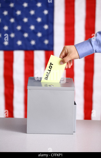 Hand putting ballot into ballot box, voting concept, American flag background - Stock-Bilder