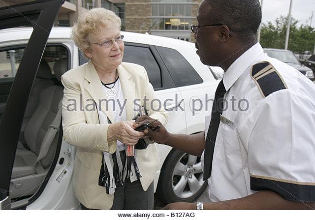 Montgomery Alabama Renaissance Hotel valet parking woman Black teen job tip uniform car keys attendant service - Stock Image