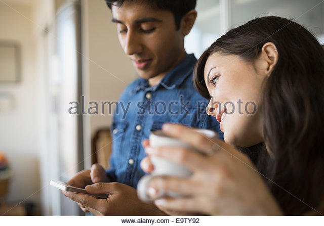 Couple with coffee and cell phone - Stock Image