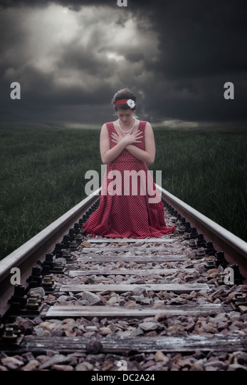 a girl in a red dress is sitting on railway tracks - Stock Image