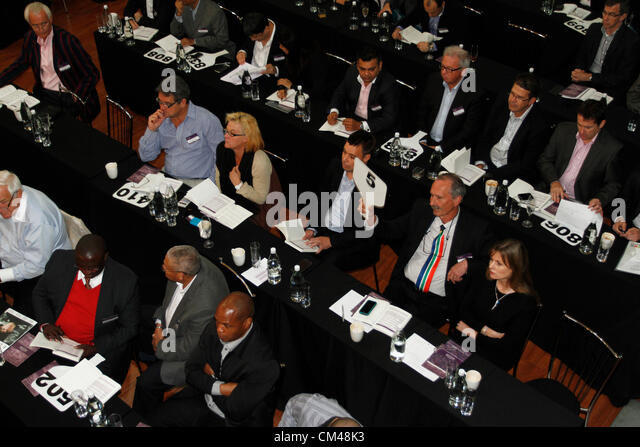 A man wearing a South African tie puts in his bid at the annual Nederburg Wine Auction, Paarl, South Africa. - Stock Image