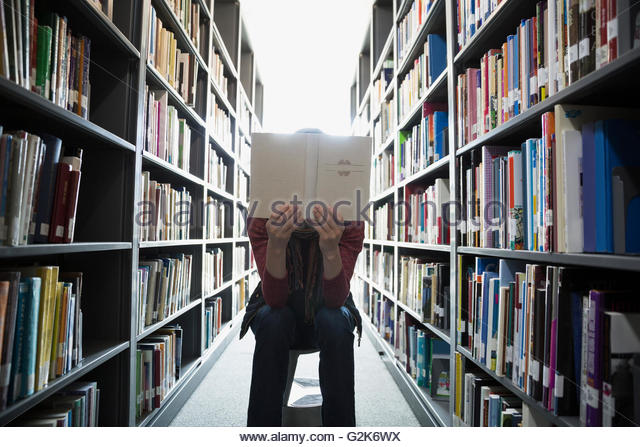 Adult education student reading between library bookshelves - Stock Image