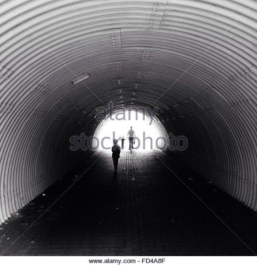 People Walking Through Tunnel - Stock Image