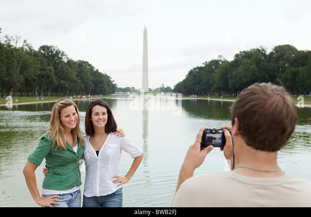 Young man taking photograph of friends at washington monument - Stock Image