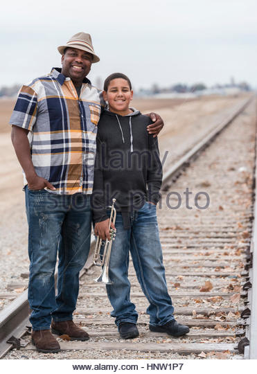 Smiling father and son standing on train track with trumpet - Stock-Bilder