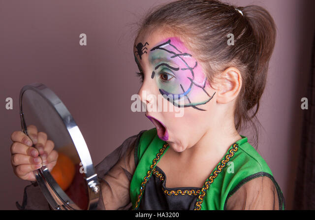 Little girl looking surprised into the mirror after face painting session before halloween party - Stock Image