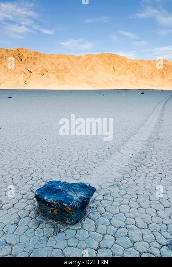 A rock leaves a trail of its movement across the The Racetrack in Death Valley National Park at sunset, CA. - Stock Image