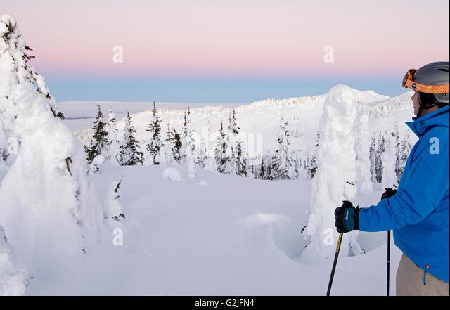 A skier among snow ghosts surveys beautiful landscape before sunrise top Sun Peaks Resort Thompson Okangan region - Stock Image