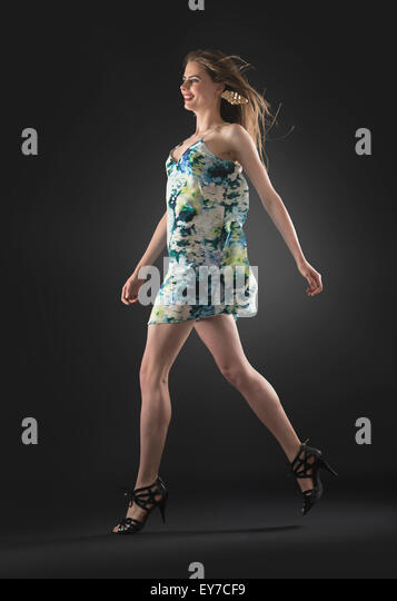 Studio shot of young woman walking - Stock Image