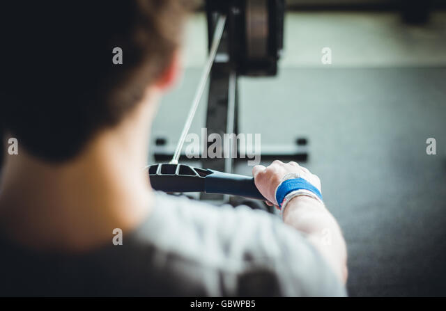 POV of young man in twenties working out in the gym alone on a rowing machine. - Stock Image