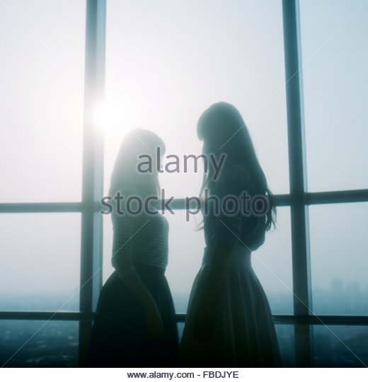 Side View Of Two Girls Standing Against Window - Stock Image