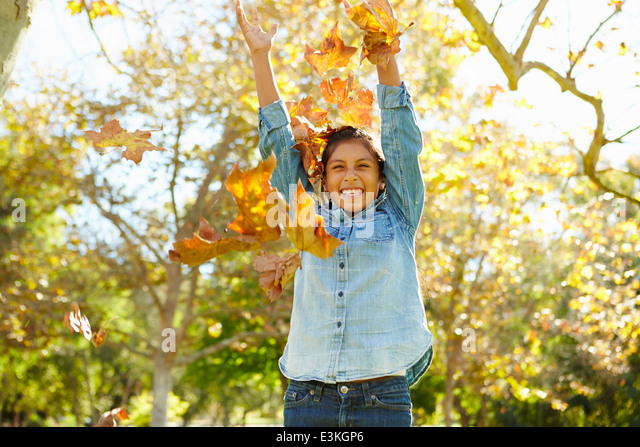 Young Girl Throwing Autumn Leaves In The Air - Stock Image
