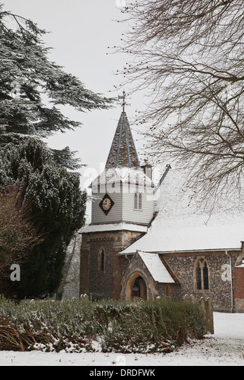 The country churchyard and village Church of St Mary The Less, Chilbolton, Hampshire, in snow - Stock Image
